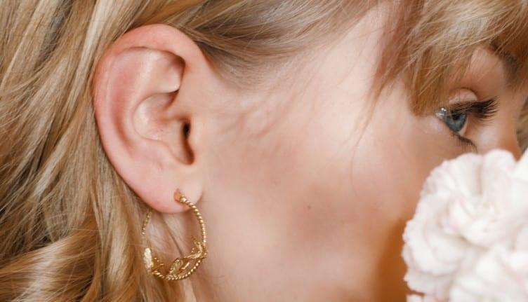 Χρυσά σκουλαρίκια μικροί κρίκοι σε γυναίκα