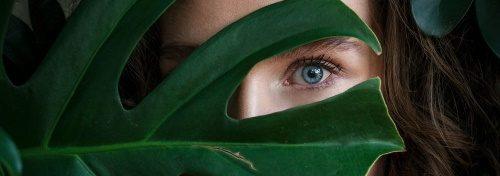 Γυναικείο πρόσωπο πίσω από φύλλο δέντρου