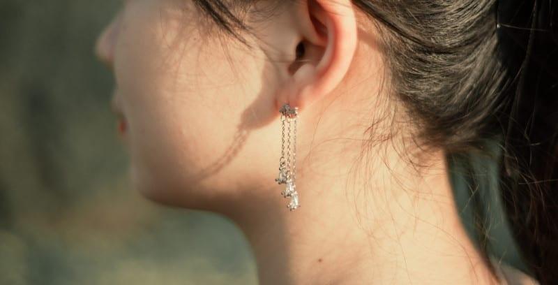 Κρεμαστά κοντά ασημένια σκουλαρίκια σε κοπέλα
