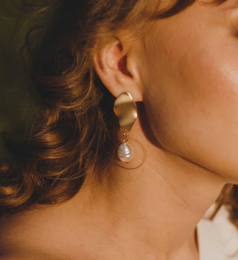 Χρυσά κοντά κρεμαστά σκουλαρίκια με έντονη λεπτομέρεια στο τέλος, σε μελαχρινή γυναίκα
