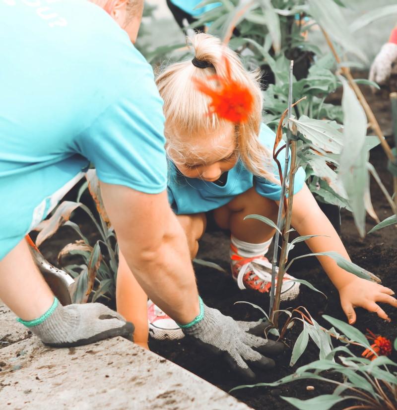 Άντρας και παιδί ασχολούνται με το χώμα και λουλούδια