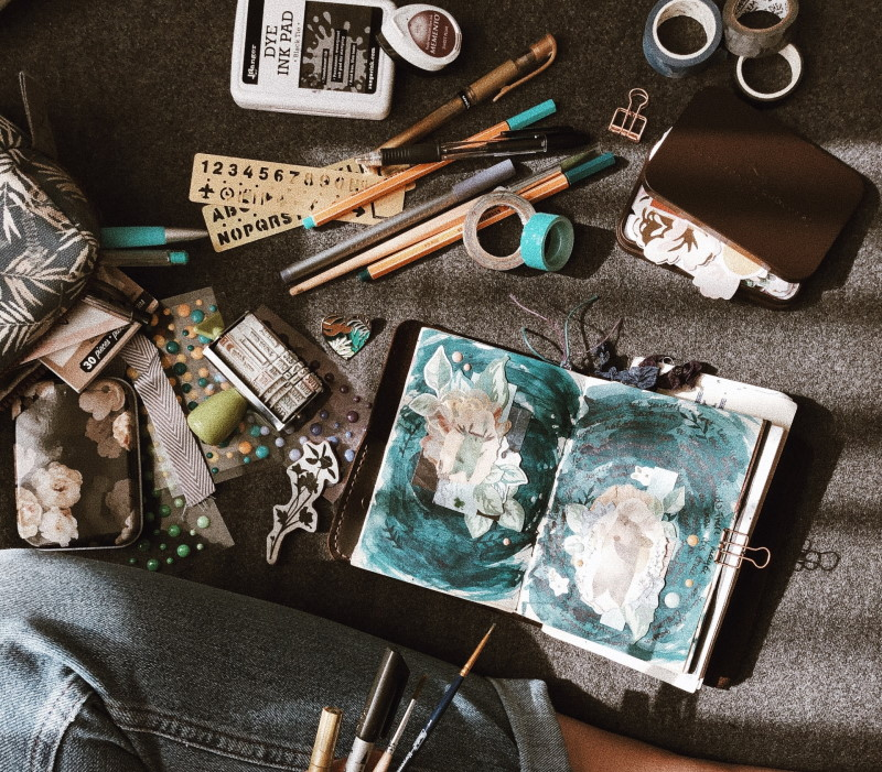 Γυναίκα με πινέλα μπροστά σε ένα scrapbook και διάφορα υλικά