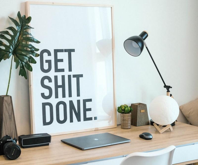 Φωτιστικό επάνω σε γραφείο δίπλα σε κάδρο που γράφει Get shit done